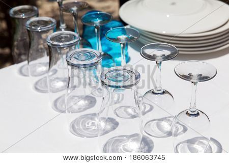 glassware, dishware and objects concept - many clean glasses upside down on table