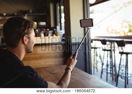 Man taking selfie from mobile phone in restaurant