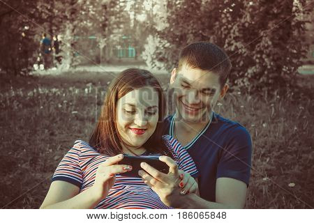 Young happy couple with smartphone, outdoors.Park. Greenscreen smartphoneSlowmotion