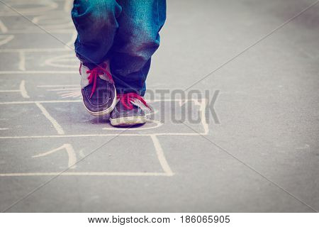 little boy playing hopscotch outdoors, kids playtime