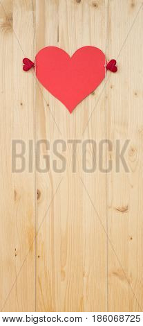 Two hearts with clothes pegs and red paper heart on a cord on wood