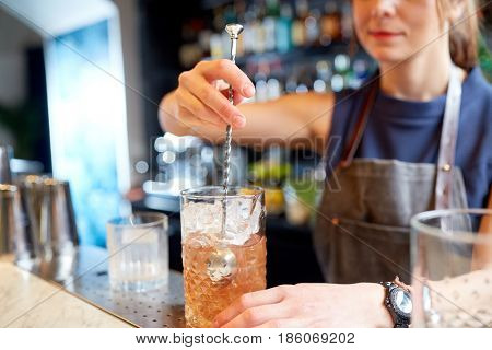 alcohol drinks, people and luxury concept - woman bartender with stirrer and glass preparing cocktail at bar counter