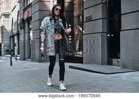 Fashion is her life. Full length of young attractive woman adjusting her denim jacket while walking down the street