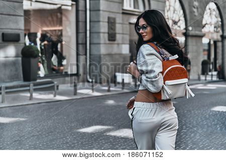 Irresistible woman. Rear view of young woman looking over her shoulder while walking outdoors