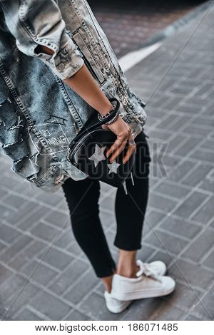 Fashionable girl. Close-up rear view of young woman carrying a purse while walking down the street