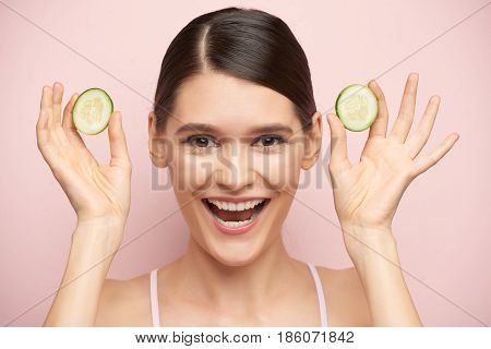 Joyful young woman showing slices of fresh cucumber