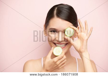 Happy girl with two slices of cucumber, isolated on pink