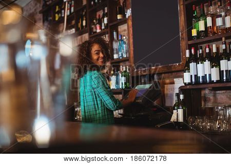 Portrait of beautiful female bar tender using electronic machine at bar counter