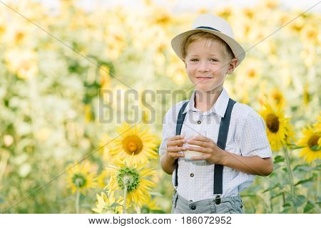 Adorable blond toddler boy drinking milk on summer sunflower field outdoors. Kids portrait. Summer countryside agriculture