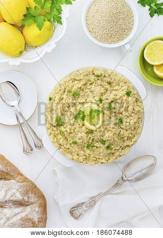 Cooked Quinoa with uncooked by the side in a vertical over head image with lemons herbs and sliver wear,on a white wooden backgound .