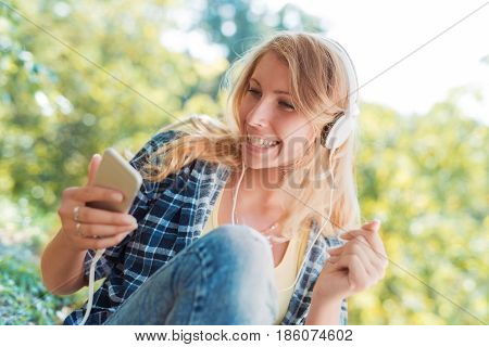 Young woman listening to music on a smart phone in the park.