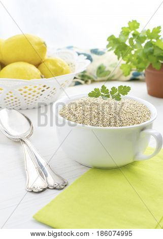 composition of uncooked Quinoa, in a vertical bright and airy image with lemons and herbs, green and  yellow colors,white background at the top for copy space