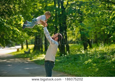 A young father throws his young son in the morning sunshine. Father's Day.