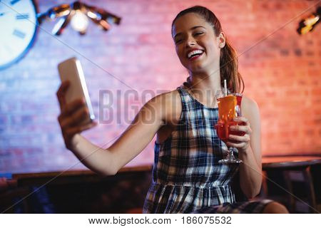 Young woman using mobile phone while having cocktail drink in pub
