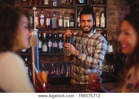 Bartender mixing a cocktail drink in cocktail shaker at pub