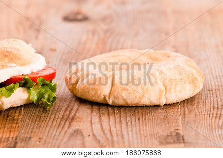Puccia bread with mozzarella and tomato on wooden table.