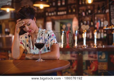 Upset woman sitting with hands on forehead in pub