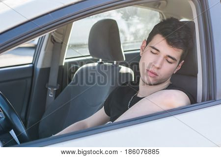 Handsome young man sleeping at the wheel driving his car. Danger concept
