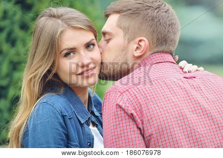 Young beautiful girl staring at camera while being kissed by her boyfriend. Close up portrait. Love, relationship, family and people concept - smiling couple hugging in park