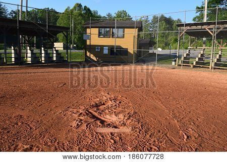 pitchers mound at base ball field showing home plate and empty bleachers