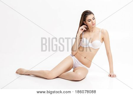 young beautiful brunette woman with perfect body in white underwear. sitting on floor on white background