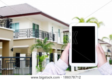 Hand holding tablet with blank on screen over blurred house background smart home concept template