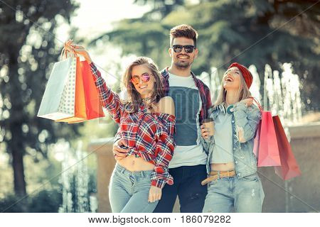 Three friends holding colored bags in hand on the way to the Mall for shopping