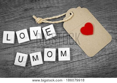 Love you mom wording with red heart sign and paper label on old wooden textured background Mother's day concept.