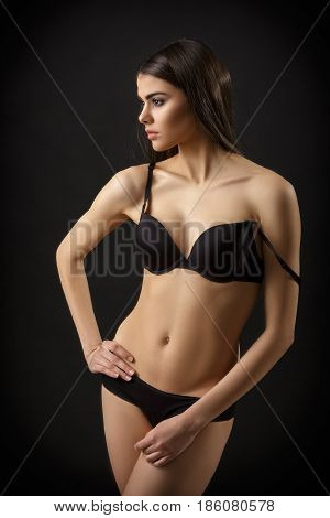 beautiful sexy brunette woman posing in black lingerie on the black background. Seductive and attractive slim shapely body
