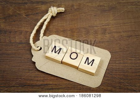 Mom wording with paper tag on old wooden textured background Mother's day concept.