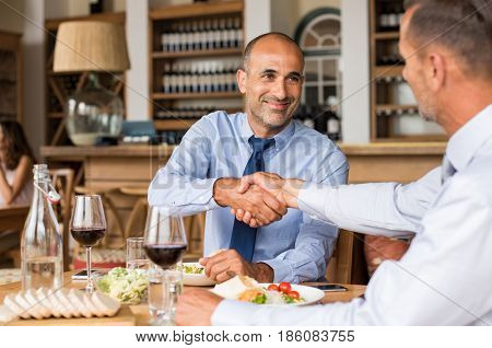 Business people shaking hands during lunch. Happy mature businessman shaking hands with employee. Handshake confirmation done by partners for signing deal while having lunch.