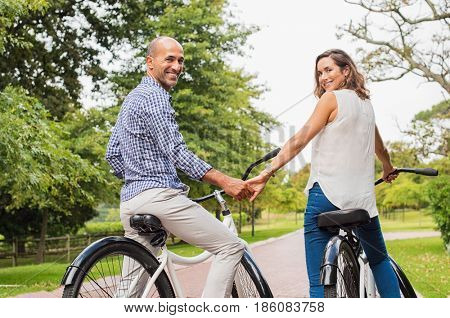 Couple sitting on bicycle while looking behind holding hands. Mature romantic couple riding bicycle in park and looking at camera. Happy multiethnic couple holding hands and riding a bike.