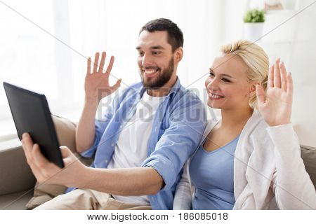 family, technology, internet, online communication and people concept - smiling happy couple with tablet pc computer having video chat and waving hands at home