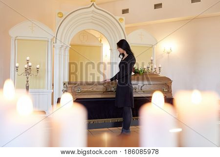 burial, people and mourning concept - sad woman with coffin at funeral in orthodox church