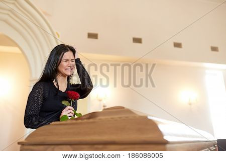 burial, people and mourning concept - crying unhappy woman with red rose and coffin at funeral in church