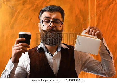 Bearded man long beard. Brutal caucasian unshaven serious hipster with glasses and moustache holding black plastic coffee cup or mug and meal box on brown studio background