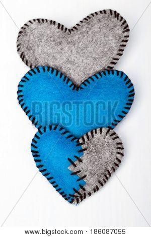 Three felt hearts on a white wooden background valentines composition