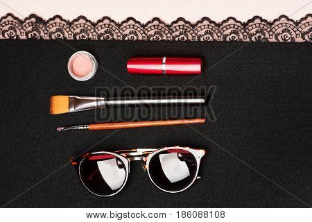 Sunglasses and makeup. Collection holding red lipstick vintage sunglasses pink matte eyeshadows and brushes on black cloth with lace on beige blackground top view