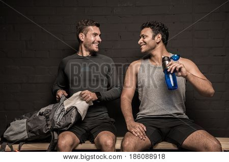 Handsome Young Athletes Resting At Gym Locker Room