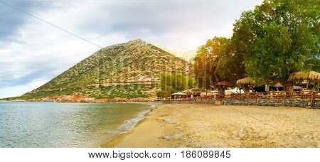 Sunny sandy Livadi beach in sea bay of resort village Bali in may. Views of mountain shore washed by waves where sunbathing tourists. Bali Rethymno Crete Greece