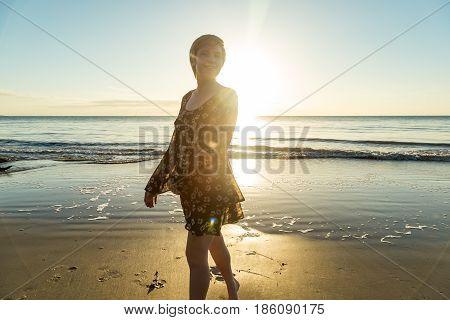 A young woman walks along the beach enjoying an early morning sunrise at Driftwood Beach, Jekyll Island, Georgia.