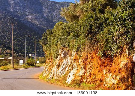 Mountain road cut through rock. Slice mountain shale texture of stone mountain wall. Stone trail in mountain dangerous path to top of stone landslides. Village Bali Crete island Greece