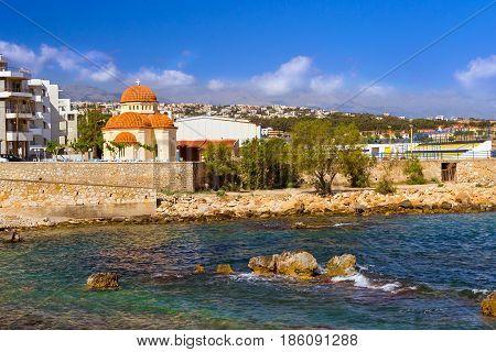 Eastern Orthodox Church of Holy Chapel Of Saint Nicholas. Place of worship on coast of Kolpos Almirou in Greek resort Rethymno. Promenade Leof. Emmanouil Kefalogianni is washed by Cretan sea. Greece