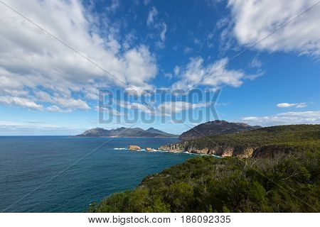 View from Cape Tourville Lighthouse lookout - Seascape photo, cliff coastline, green mountain, blue sky at Freycinet National Park, Tasmania, Australia