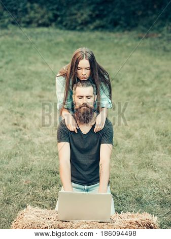 Girl And Bearded Man Using Laptop On Nature