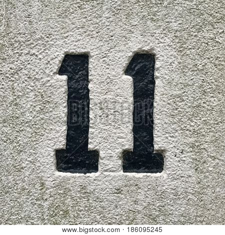 Number 11 painted black house number address sign on painted white stone wall textured background