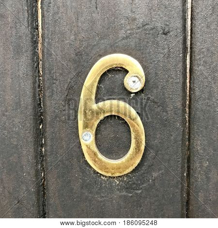 Number 6 gold metal house address number sign screwed into painted black wood fence gate door textured background