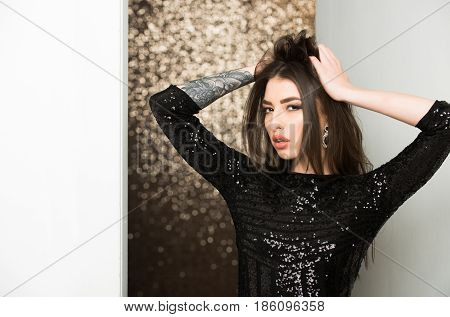 fashion model woman or cute girl with stylish makeup long brunette hair in sequin black dress posing with tattoo on hand on brown glittering bokeh background. Party holiday celebration
