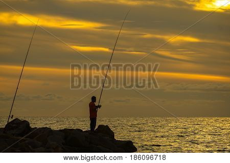 Silhouette of people enjoying the Surf fishing with background of beautiful sunset.Surf fishing is the sport of catching fish standing on the shoreline or wading in the surf.