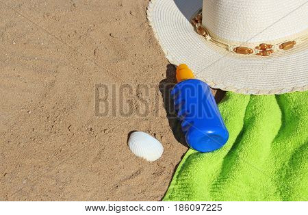 at the beach lady's sunhat towel sunmilk and a sea shell lying in the sand